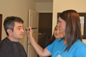 Lori gets Aziz ready for his scene on the men's testimony and cooking show.